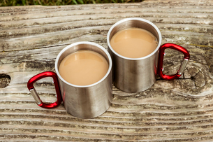Two metal camping mugs of tea on a wooden table.の写真素材 [FYI02266234]