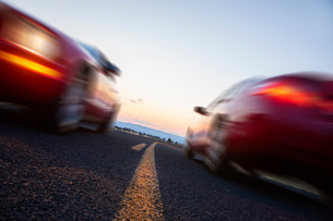 A low angle view of two cars blurred and passing each other going opposite ways on a highway.の写真素材 [FYI02266238]