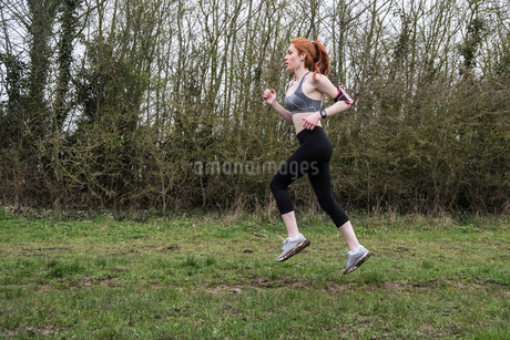 Young woman with long red hair wearing sports kit, exercising outdoors.の写真素材 [FYI02266241]