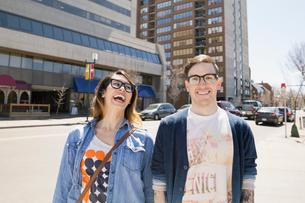 Hipster couple laughing on sunny urban streetの写真素材 [FYI02266244]