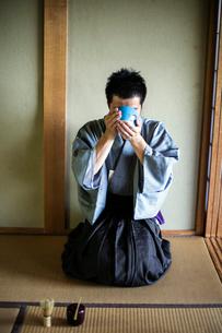 Japanese man wearing traditional kimono kneeling on floor, raising blue tea bowl during tea ceremonyの写真素材 [FYI02266245]