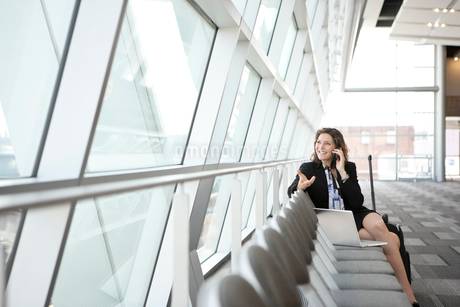 Caucasian businesswoman using her cell phone while sitting in a row of chairs against a window in aの写真素材 [FYI02266248]