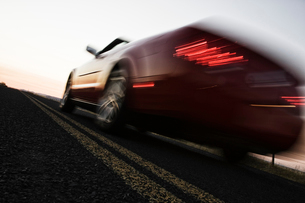 A low angle blurred view of a convertible sports car silhouetted on the road at sunset.の写真素材 [FYI02266249]