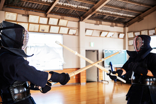 Two Japanese Kendo fighters wearing Kendo masks practicing with wood sword in gym.の写真素材 [FYI02266261]