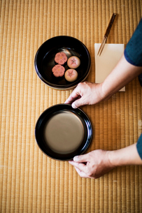 High angle close up of man knelling on floor, holding a bowl with Wagashi, sweets traditionally servの写真素材 [FYI02266263]