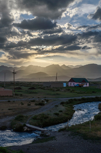 Sunset over cottage by a river with distant mountains, Sary Moghul, Kyrgyzstan.の写真素材 [FYI02266294]
