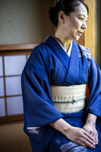 Japanese woman wearing traditional bright blue kimono with cream coloured obi kneeling on floor in tの写真素材 [FYI02266302]
