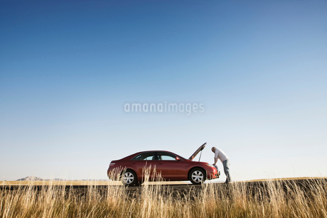 A man looking into the engine compartment of his car parked along a highway in eastern Washington Stの写真素材 [FYI02266304]