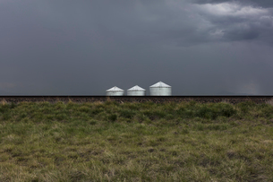 Grain silos and storm clouds over vast farmland and prairie, train tracks in foregroundの写真素材 [FYI02266308]