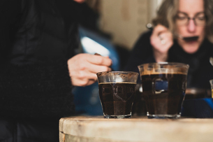 Close up of two glasses with coffee standing on wooden table, people in background.の写真素材 [FYI02266315]