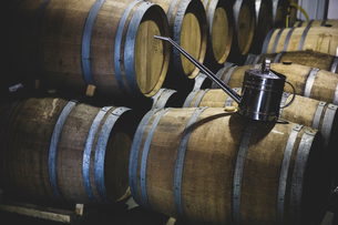 Stainless steel can on top of oak wood wine barrels in a cellar during the winemaking process.の写真素材 [FYI02266316]