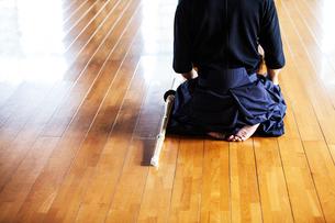 Rear view of Japanese Kendo fighters kneeling on wooden floor.の写真素材 [FYI02266318]