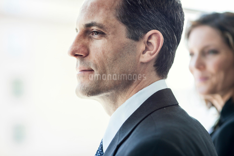 Close-up of a Caucasian businessman looking out the widow of a conference centre lobby.の写真素材 [FYI02266319]