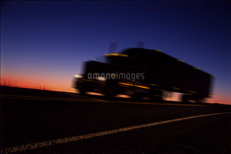 A sleeper truck silhouetted on road at sunrise, an orange light on the horizon.の写真素材 [FYI02266324]