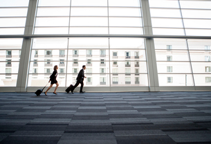 Male and female business people running past a window in the lobby of a conference centreの写真素材 [FYI02266325]