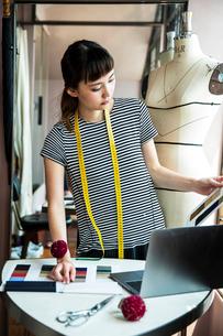 Japanese female fashion designer standing at desk, working in her studio.の写真素材 [FYI02266328]
