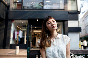 Japanese woman with long brown hair wearing white short-sleeved blouse sitting on a bench, wearing eの写真素材 [FYI02266338]