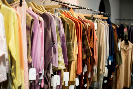 A hanging rail of women's clothing dyed using natural plant dyes, on a rail in a store.の写真素材 [FYI02266339]