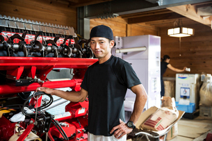 Japanese farmer wearing black cap standing next to agricultural machine, smiling at camera.の写真素材 [FYI02266343]