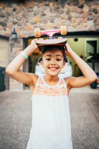 Smiling girl standing in driveway in front of house with skateboard on her headの写真素材 [FYI02266345]