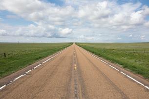 Open road through vast prairie and farmland, Saskatchewan, Canada.の写真素材 [FYI02266355]