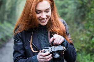 Smiling young woman with long red hair walking along forest path, taking pictures with vintage camerの写真素材 [FYI02266357]