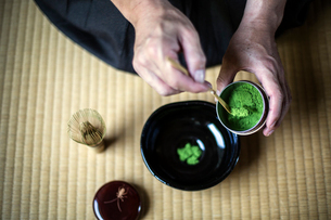 High angle close up of traditional Japanese Tea Ceremony, man spooning green Matcha tea powder intoの写真素材 [FYI02266361]