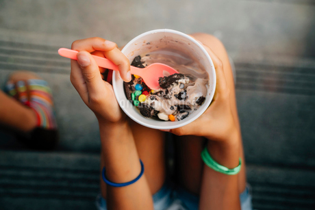 High angle close up of girl sitting on steps eating ice creamの写真素材 [FYI02266382]