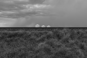 Grain silos and storm clouds over vast farmland and prairie, train tracks in foregroundの写真素材 [FYI02266385]