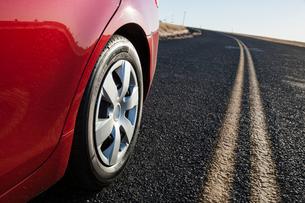 A low angle view of a rear tire on a car as it drives on the highway.の写真素材 [FYI02266386]