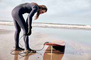 Man preparing to surf on a sandy beach in a wetsuit.の写真素材 [FYI02266391]