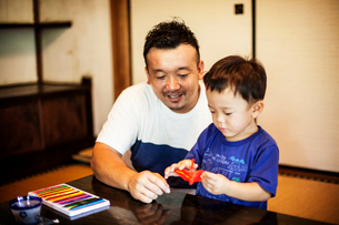Japanese man and little boy sitting at a table, making Origami animals using brightly coloured paperの写真素材 [FYI02266399]