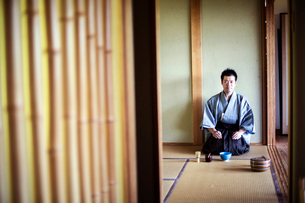Japanese man wearing traditional kimono kneeling on tatami mat during tea ceremony.の写真素材 [FYI02266400]