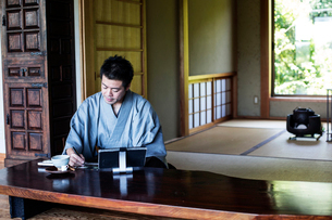 Japanese man wearing kimono sitting on floor in traditional Japanese house, looking at digital tableの写真素材 [FYI02266415]