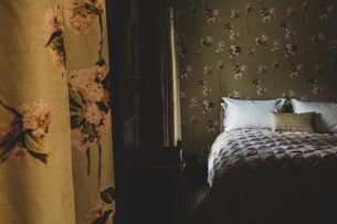 Interior view of bedroom with curtains and wallpaper with floral pattern, pale pink quilt and whiteの写真素材 [FYI02266416]