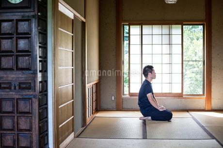 Japanese man kneeling on tatami mat in traditional Japanese house.の写真素材 [FYI02266425]