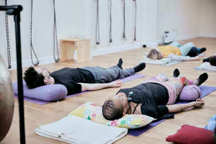 People lying down on an exercise studio floor relaxing after a sound therapy sessionの写真素材 [FYI02266431]