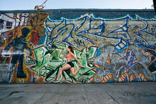 Female athlete running along sidewalk past building covered in graffiti.の写真素材 [FYI02266433]