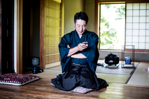 Japanese man wearing kimono sitting on floor in traditional Japanese house, using mobile phone.の写真素材 [FYI02266435]