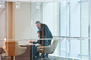 An Asian businesswoman and a Caucasian businessman at work at a conference table.の写真素材 [FYI02266439]
