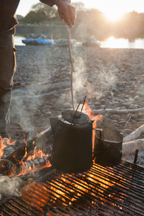 A man checks a pot of coffee on a rack over a campfire on a river camping tripの写真素材 [FYI02266440]