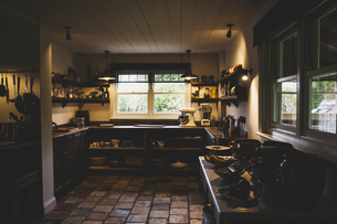 Interior view of kitchen with stone tile floor, wooden ceiling and two sash windows, antique woodenの写真素材 [FYI02266441]