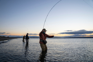 Two fly fishermen cast for searun coastal cutthroat trout and salmon with their guide standing betweの写真素材 [FYI02266444]