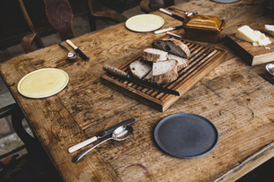 High angle close up of plates, cutlery and bread on a vintage wooden table.の写真素材 [FYI02266445]