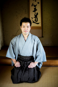 Japanese man wearing kimono sitting on floor in traditional Japanese house, looking at camera.の写真素材 [FYI02266449]