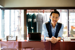 Japanese salesman with moustache wearing glasses standing at counter in clothing store, smiling at cの写真素材 [FYI02266451]