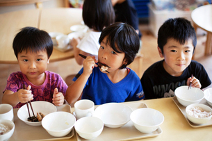 High angle view of three boys sitting at a table in a Japanese preschool, eating with chopsticks.の写真素材 [FYI02266461]