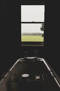 Interior view of bathroom with sash window, roll top bath with brass bath caddy.の写真素材 [FYI02266464]