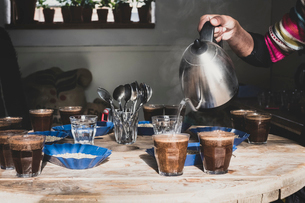 Coffee tasting, barista pouring coffee into glasses on a wooden table, trays with coffee beans.の写真素材 [FYI02266466]