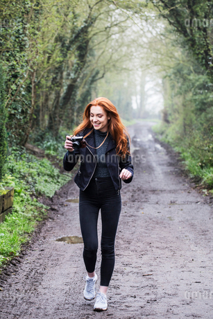 Smiling young woman with long red hair walking along forest path, taking pictures with vintage camerの写真素材 [FYI02266476]